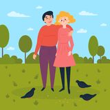 Young couple in the park with pigeons around. Young couple in the park. Man and woman have a date in summer or spring day time. Pigeon birds and seeds on the Stock Photo