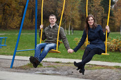 Young couple in the park on swing stock photos