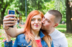 A Young couple in a Park taking picture of themselves Stock Photography