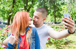 Young couple in a Park taking picture of themselves Stock Photo