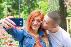 Young couple in a Park taking picture of themselves Stock Photography