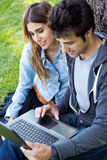 Young couple at the park using a laptop Royalty Free Stock Image