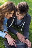 Young couple at the park using a laptop Stock Photos