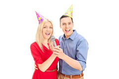 Young couple with party hats singing on microphone Stock Images