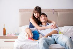 The young couple partying in the bed. Young couple partying in the bed royalty free stock photo