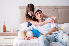 The young couple partying in the bed Stock Image