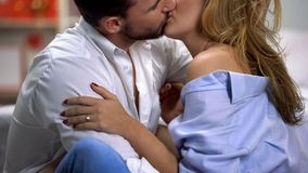 Young couple passionately kissing, sitting on floor in bedroom, togetherness stock photos
