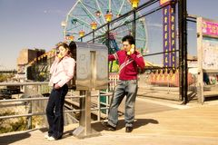 Young couple on pay phone. Young couple using pay phones at Coney Island Royalty Free Stock Photo
