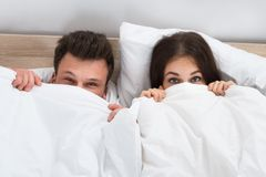Young couple peeking from bedsheets Royalty Free Stock Image