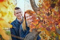 Young couple peeking from behind tree Stock Photography