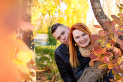 Young couple peeking from behind tree Royalty Free Stock Photo