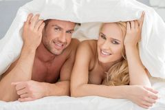 Young couple peeking out from under the bedclothes Royalty Free Stock Photos