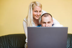 Young couple peeking over laptop screen Royalty Free Stock Photo