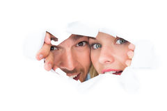 Young couple peeking through torn paper Stock Image