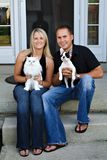 Young Couple and Pets. A young couple sits in front of their home with their pet cat and puppy Stock Photography