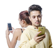 Young couple with phone addiction. Young couple with smart  phone addiction isolated on white Royalty Free Stock Photography