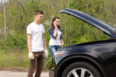 Young couple phoning for roadside assistance. After their car has broken down standing looking into the engine compartment with the bonnet up Stock Photography