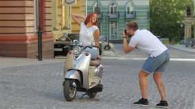Young couple photographed on a scooter. Portrait of happy young love couple photographed on a scooter and enjoying themselves in the city at summer time stock video footage