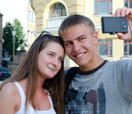 Young couple photographing themselves. In front of urban buildings witha compact digital camera Stock Photo