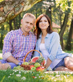 Young couple on a picnic eating fruits Royalty Free Stock Photo