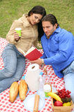 Young Couple Picnic Outdoor. Shot of couple reading and enjoying picnic summer day outdoor stock photo