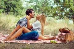 Young couple on picnic, sitting face to fa Royalty Free Stock Image