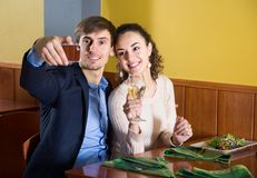 Young couple pictures of yourself on your smartphone for dinner. Young cute pictures of yourself on your smartphone for dinner in a restaurant Stock Photo