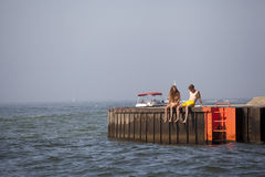 Young couple on a pier on Lake Michigan. Young couple sitting on pier on Lake Michigan during the warms days of summer Stock Photo
