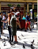 Young couple with pigeons in Bath, near the Roman Bath. Royalty Free Stock Photo