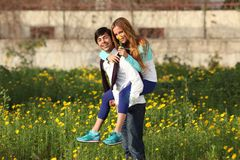 Young couple piggy-backing in meadow Stock Photography