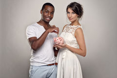 Young Couple with Piggy Bank Smiling at the Camera Stock Image