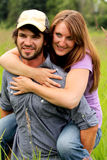 Young Couple Piggyback. A young man giving his girlfriend a piggy back ride in a field of tall grass.  Shallow depth of field Royalty Free Stock Photography