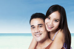 Young couple piggyback at beach Stock Photos