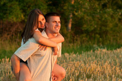 Young couple piggyback riding and watching sunset Royalty Free Stock Photography