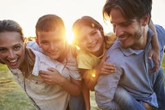 Young couple piggybacking their young children outdoors royalty free stock photography
