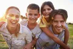 Young couple piggybacking their kids outdoors look to camera Royalty Free Stock Photo