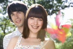 Young couple with pinwheel, smiling, portrait (blurred motion) Royalty Free Stock Photos