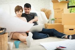 Young couple planning their new house. Happy young couple with laptop and blueprints planning their new moving house royalty free stock images