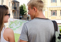 Young couple planning their sightseeing. Rear view of a young couple looking at a map and planning their sightseeing Royalty Free Stock Image