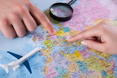 Couple planning vacation trip with map. Top view. Young couple planning vacation trip with map to Europe. Top view royalty free stock photos