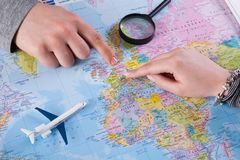 Couple planning vacation trip with map. Top view. Young couple planning vacation trip with map to Germany, Europe. Top view royalty free stock photography