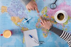 Couple planning vacation trip with map. Top view. Young couple planning vacation trip with map to United Kingdom, Europe., taking notes in blank notebook, copy royalty free stock photography