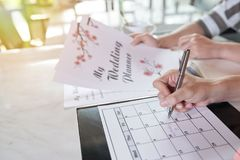 Planning Wedding Day. Young couple planning wedding day together and taking necessary notes in calendar while sitting at home, close-up shot stock photo