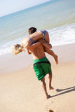 Young couple play on beach. In the sun royalty free stock photography