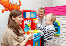 Young couple play toy kitchen with little boy. At home Stock Photos
