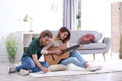 Young couple playing acoustic guitar and composing song in room. Young couple playing acoustic guitar and composing song in living room stock photography