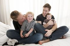 Young couple playing with baby girl and little child. Sitting Royalty Free Stock Photo