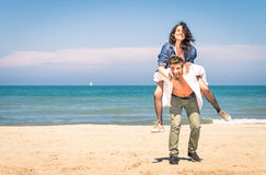 Young couple playing at the beach - Piggyback jump Royalty Free Stock Photo