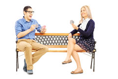 Young couple playing cards seated on wooden bench Royalty Free Stock Images