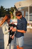Young couple playing with a cat outside at the beach at the wooden deck summer time royalty free stock images